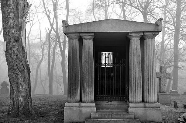 mausoleum in a very foggy graveyard - mausoleum stockfoto's en -beelden