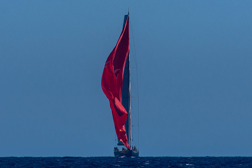 Sailing boat is shifiting red gennaker on the sea during regatta