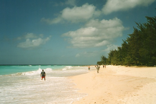 Maxwell Beach, Barbados - February 26, 2006: Tourists walking and refreshing at Maxwell beach, a long stretch of white sand  on Barbados southern coat.