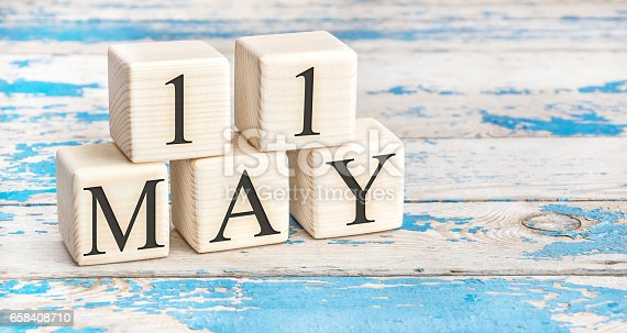 istock May 11th. Wooden cubes with date of 11 May on old blue wooden background. 658408710