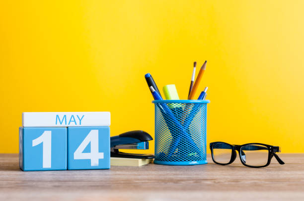 May 14th. Day 14 of month, calendar on business office table, workplace at yellow background. Spring time. Astronomy Day. World Fair Trade DAY stock photo
