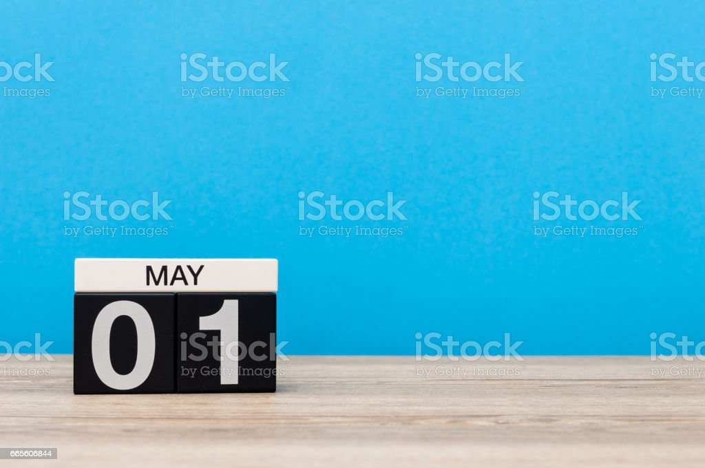 May 1st. Day 1 of month, calendar on blue background. Spring day, empty space for text. International Workers' Day stock photo