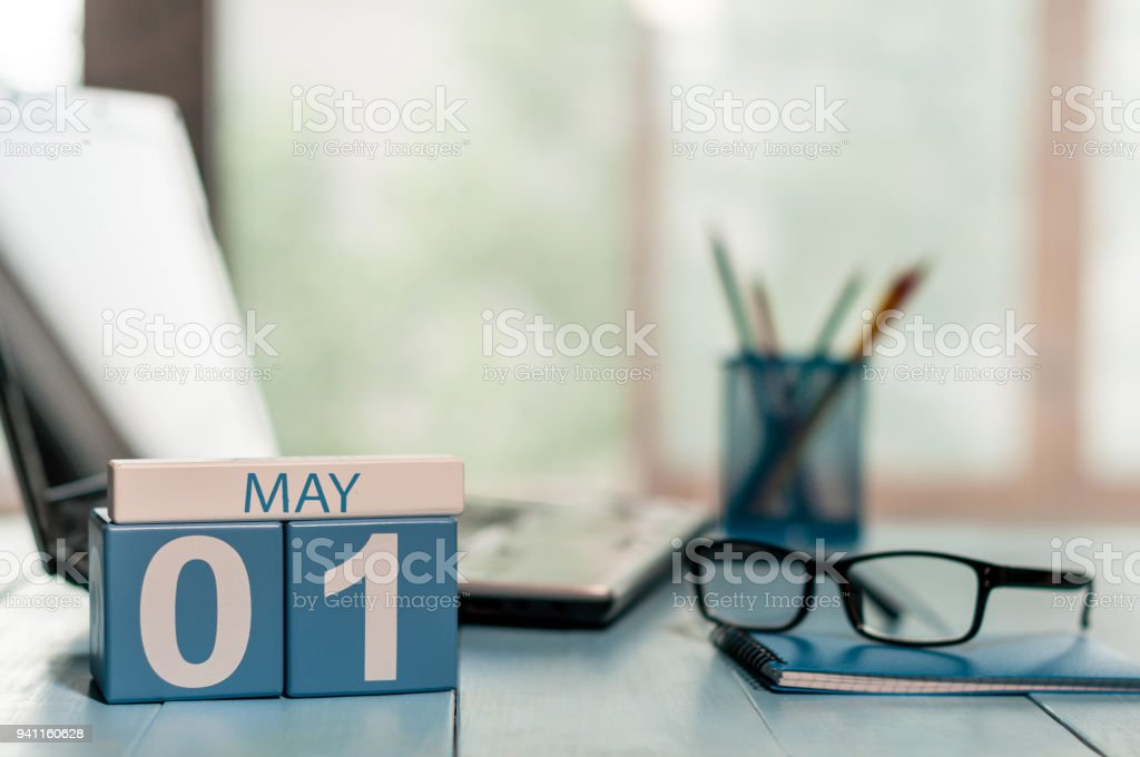 May 1st. Day 1 of month, calendar on business office background, workplace with laptop and glasses. Spring time, empty space for text stock photo