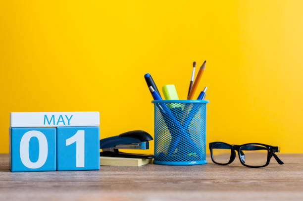 May 1st. Day 1 of month, calendar on business office table, workplace at yellow background. Spring time stock photo