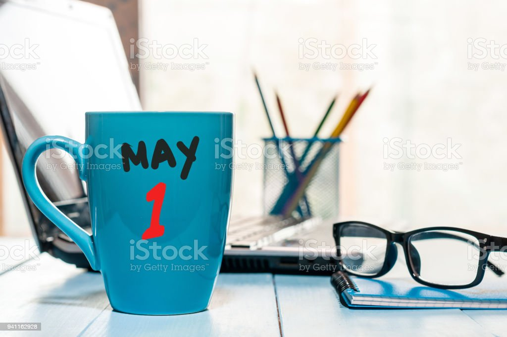 May 1st. Day 1 of month, calendar on morning coffee cup, business office background, workplace with laptop and glasses. Spring time, empty space for text stock photo