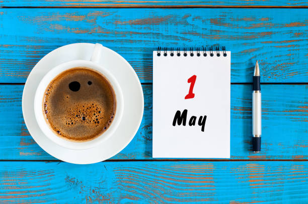 May 1st. Day 1 of month, calendar on white notepad with morning coffee cup at work place background. Top view stock photo