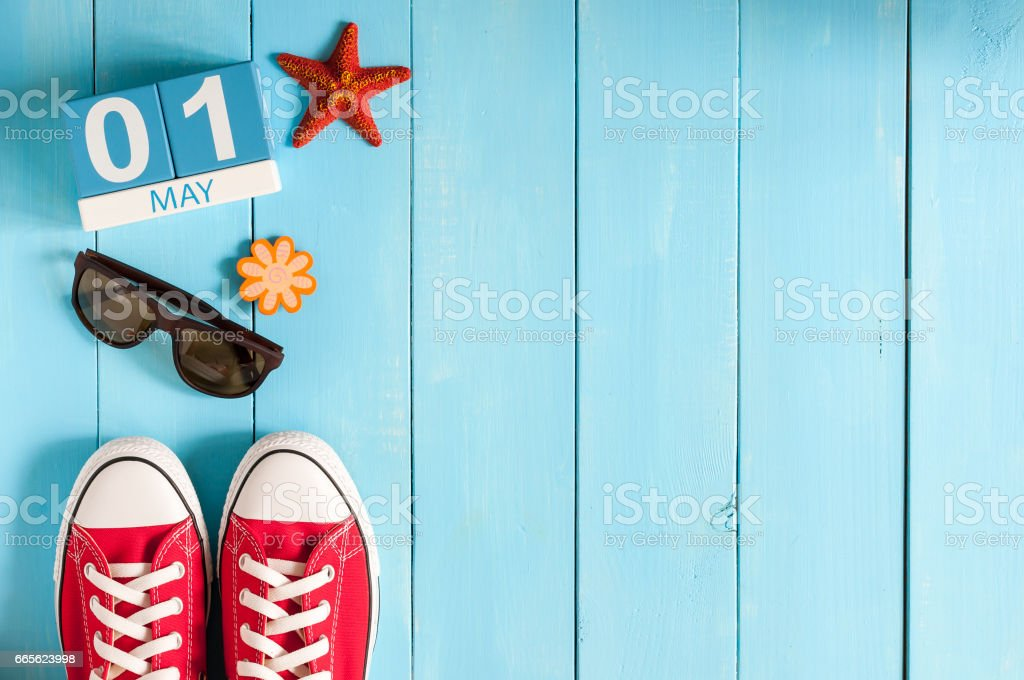 May 1st. Image of may 1 wooden color calendar on blue background.  Spring day, empty space for text.  International Workers' Day stock photo
