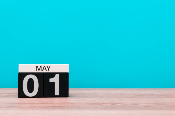 May 1st. Image of may 1 wooden color calendar on turquoise background. Spring day, empty space for text. International Workers' Day stock photo