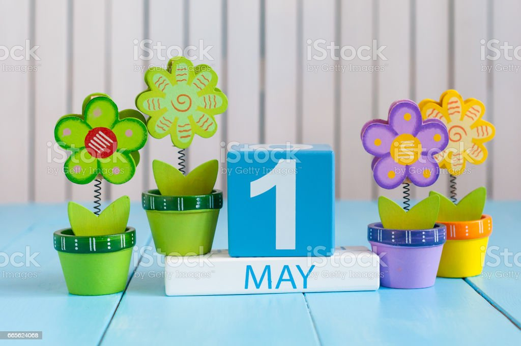 May 1st. Image of may 1 wooden color calendar on white background with flowers. Spring day, empty space for text.  International Workers' Day stock photo