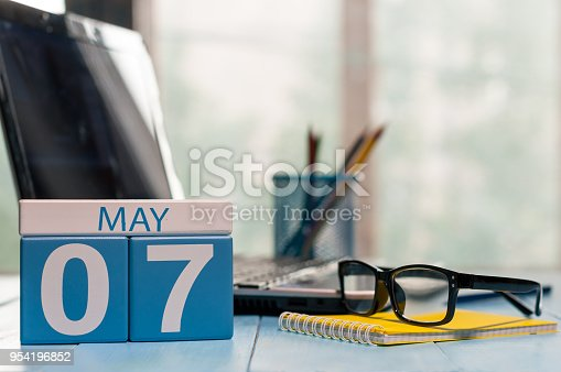 istock May 7th. Day 7 of month, calendar on business office background, workplace with laptop and glasses. Spring time, empty space for text 954196852