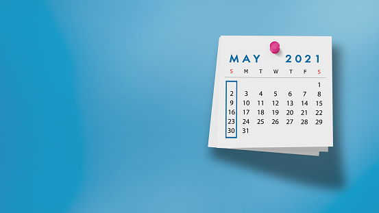 2021 May calendar on a white note paper pinned on wall against blue background. High resolution and copy space for all your crop needs.