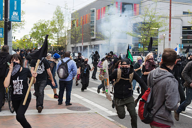 May Day Protesters in Seattle Seattle, WA, USA – May 1, 2015: Protesters run from gas grenades fired by Seattle police officers during May Day rioting on Capitol Hill. riot stock pictures, royalty-free photos & images