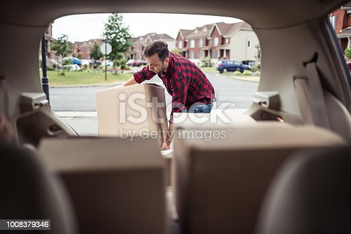 Caucasian man loading moving boxes in to his car. View from the car trunk