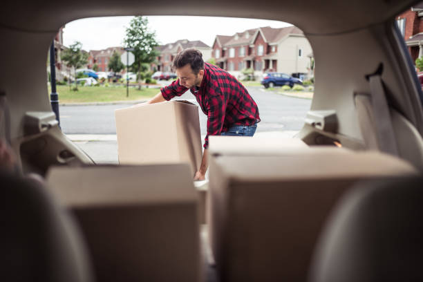 I may need help for this boxe Caucasian man loading moving boxes in to his car. View from the car trunk physical activity stock pictures, royalty-free photos & images