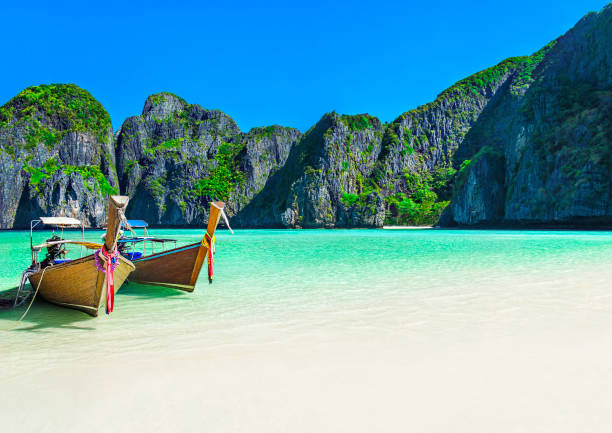 Maya Bay beach with two longtail boats, Ko Phi Phi Leh Island, Thailand stock photo