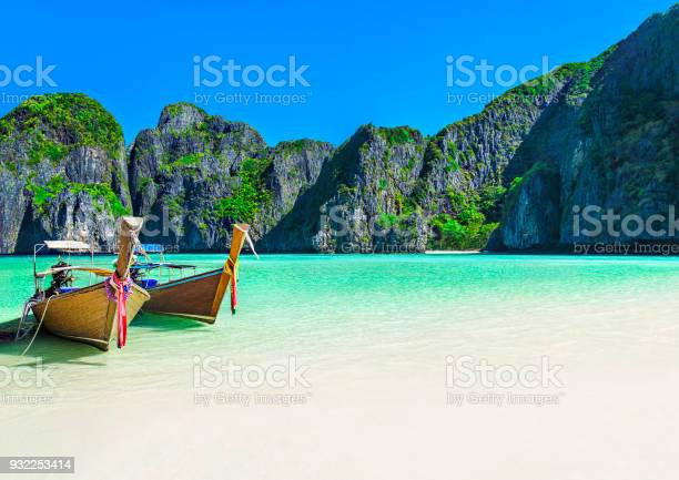 Famous scenic Maya Bay beach at Ko Phi Phi Leh Island with two traditional longtail taxi boats mooring and steep limestone hills in background, Thailand, part of Krabi Province, Andaman Sea