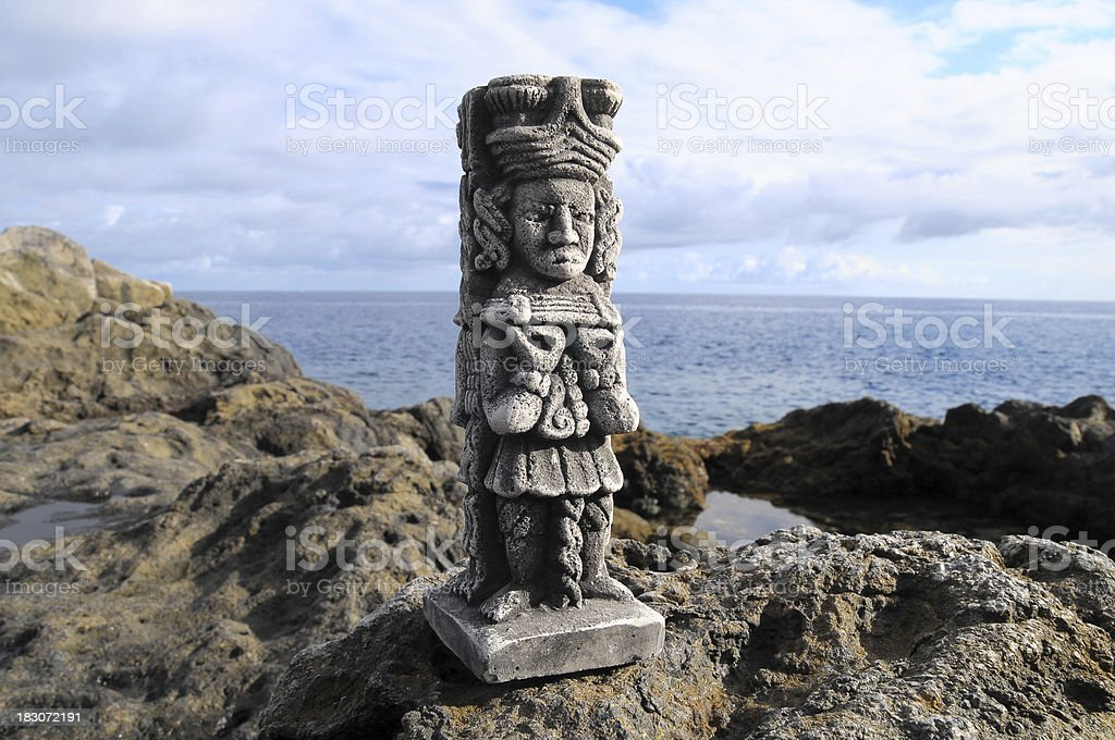 A Maya statue standing on a rock by the water royalty-free stock photo