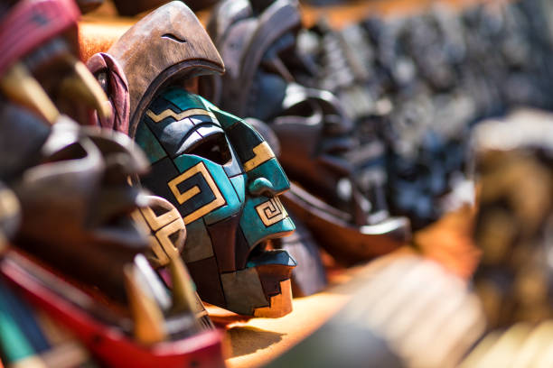 Mayan mask souvenirs for sale in Mexico Colorful wood carving traditional Mayan mask souvenirs made by local artisans sold to tourists carving craft product stock pictures, royalty-free photos & images