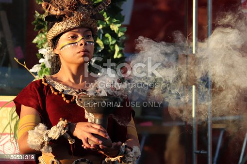 Moscow, Russia - June 2019: Girl as a Mayan Priestess performs an ancient ritual of fire on on Manezh square on Moscow historical festival Times and epochs. Performance by the Mexican group Xipetotek, reenactors of historyof Maya