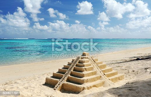 A sand castle on a central American beach of a Mayan Temple Pyramid - in the style of Chichen Itza