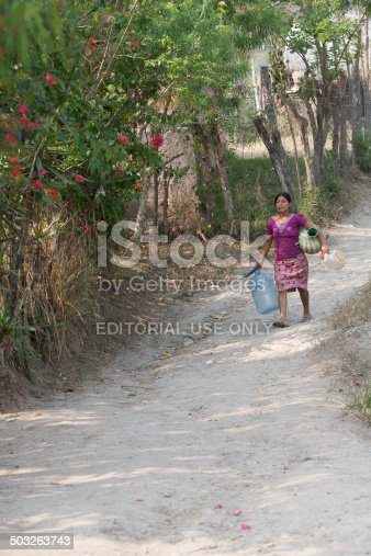 istock Mayan woman carries large bottles to fetch water 503263743