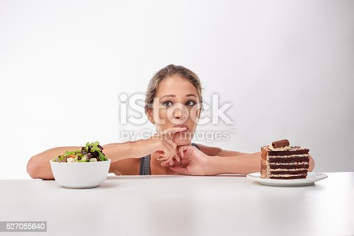 Studio shot of a woman deciding between healthy and unhealthy foods