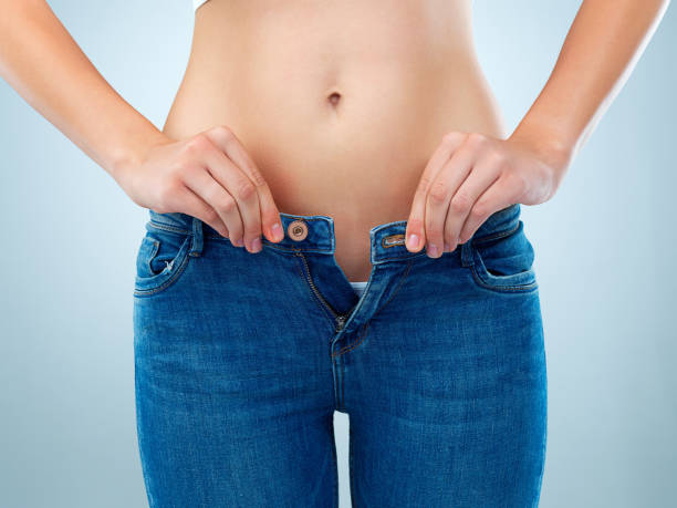 Maybe it's time for a diet Shot of an unidentifiable young woman buttoning her jeans in studio fully unbuttoned stock pictures, royalty-free photos & images