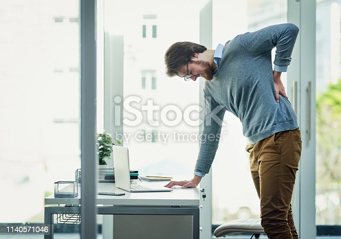Shot of a young businessman experiencing back pain while working at his desk in a modern office