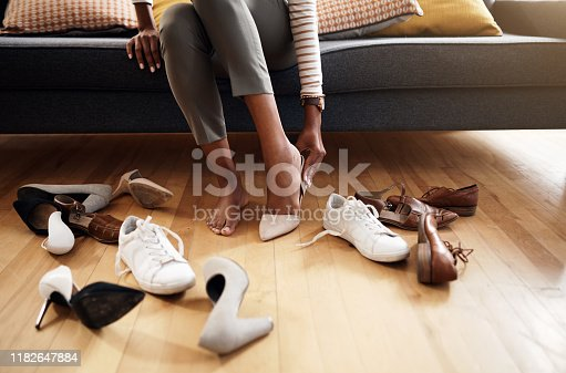Cropped shot of an unrecognizable woman trying on various shoes at home
