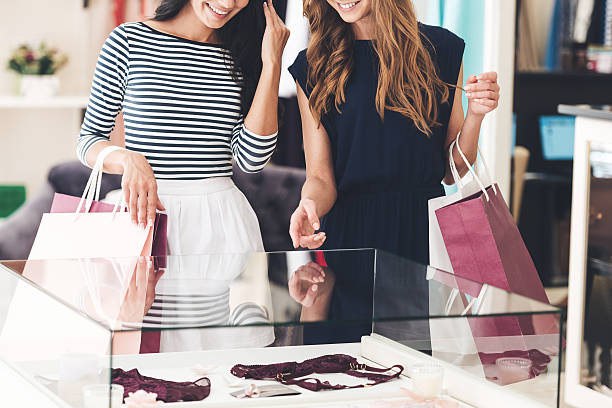 Maybe this is one? Close-up of two beautiful women with shopping bags looking at lingerie showcase with smile while standing at the store lingerie stock pictures, royalty-free photos & images