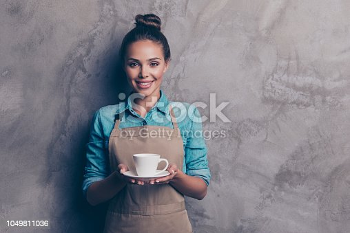 istock Maybe you want a cup of coffee Girl holding a drink stretching her palm hands forward isolated on gray textured wall background 1049811036