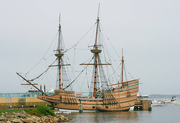 Mayflower II Sailing Ship Replica, Plymouth, Massachusetts, USA. Plymouth, MA, USA - September 10, 2007: The Mayflower II. The Mayflower II Tall Ship is a replica of the 17th century ship Mayflower, celebrated for transporting the Pilgrims to the New World. Rocks, shoreline, pier, green grass and bushes, boats moored at the harbor, tourists visiting the museum and overcast sky are in the image. pilgrim stock pictures, royalty-free photos & images