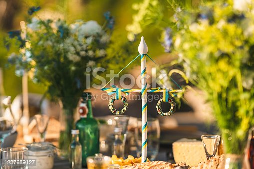 A traditional Swedish maypole decoration on the table at midsummer. Surrounded by food and flowers.