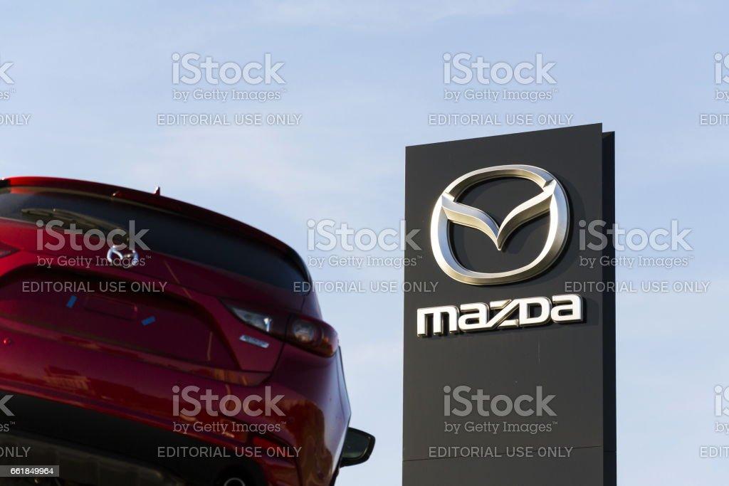Mazda 3 car in front of dealership building