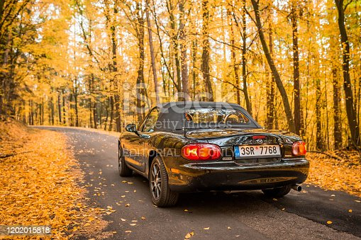 PRAGUE, CZECH REPUBLIC, OCTOBER 2019: Mazda MX-5 Miata NB second generation, model year 1999 On a forrest road in autumn with beautiful colorful fall trees in the background
