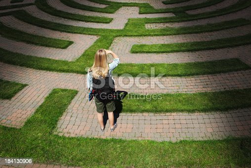 A woman teenager student stands looking through the puzzling maze of schooling and the education system, forecasting the way forward and searching for the path to her goal. Concept of student facing uncertainty to their education, life and future career.