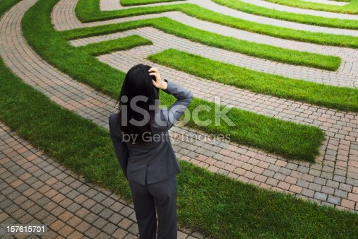 A business woman stands scratching her head, wondering in front of a grass maze, perhaps lost or searching for a solution to her business problem. Illustrates concepts for business problem-solving and management strategy, or employment and occupation issues, uncertainties, and problems.