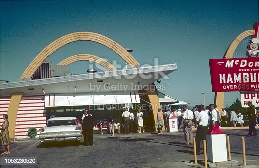 Detroit, Michigan, USA, 1962. McDonald's store in Detroit. Furthermore: visitors, consumers, advertising sign and a parking lot with cars.