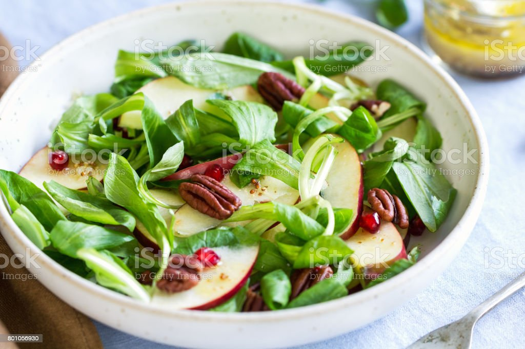 Mâche with Apple, Pomegranate and Pecan salad by vinaigrette stock photo