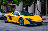 Austin, USA - November 5, 2016: A yellow colored McLaren 650S Spider convertible sports car parked on a street in downtown Austin, Texas.