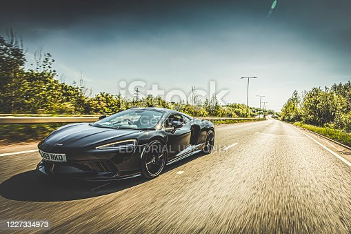 A Sunny day on a highway with a 2019 McLaren GT Super Car