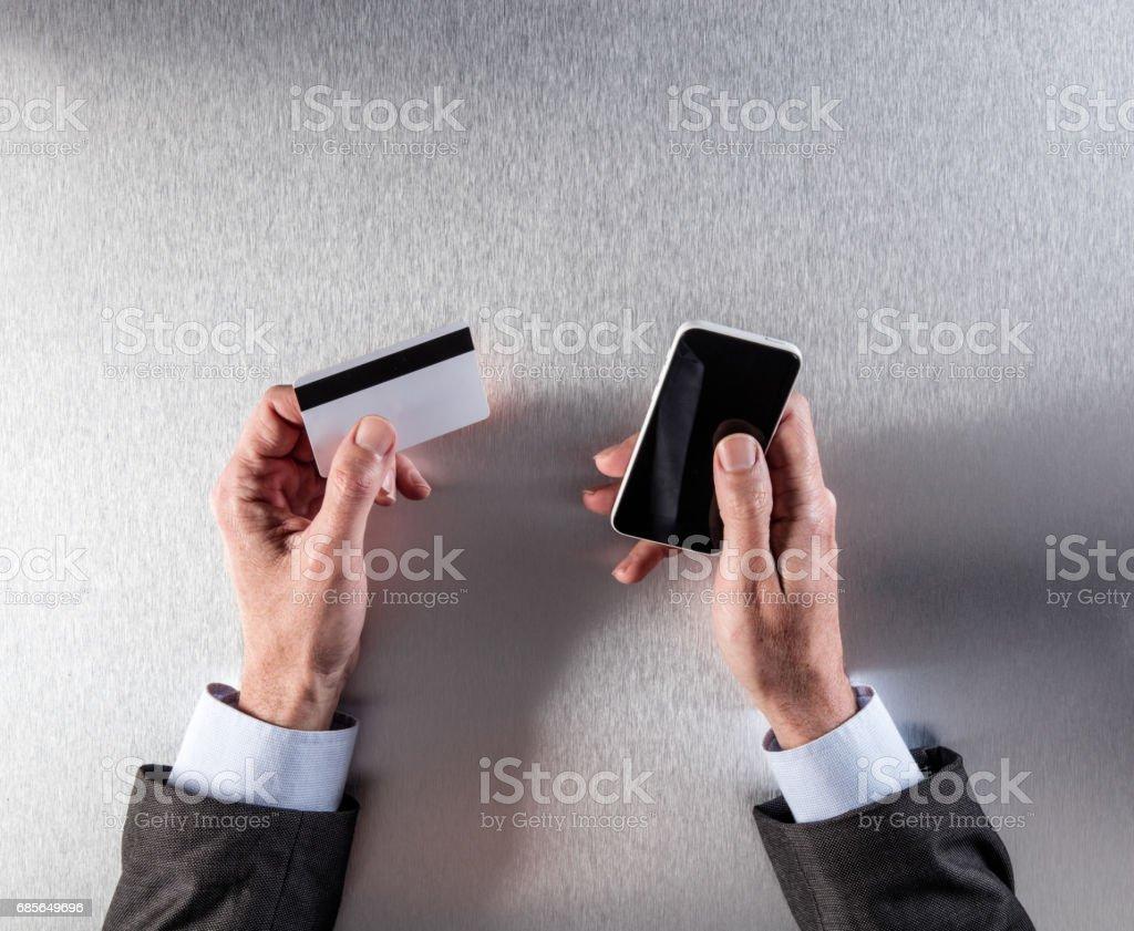 クレジット カードや携帯電話を保持している実業家の手で m コマース ロイヤリティフリーストックフォト