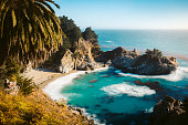 Classic postcard view of famous McWay Falls in scenic golden evening light at sunset on a beautiful sunny day with blue sky in summer, Julia Pfeiffer Burns State Park, Big Sur, California, USA