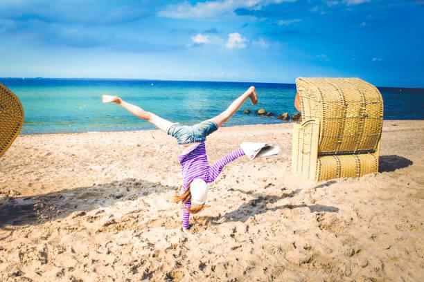 mädchen macht handstand oder schlägt rad ben strand mit zeitung in der hand küsntlerisch - newspaper beach stockfoto's en -beelden