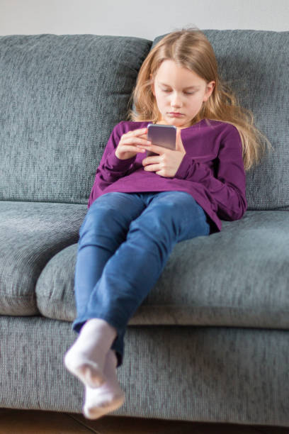mädchen tippt auf einem smartphone und sitzt auf einem schönsten sofa - lila mädchen zimmer stock-fotos und bilder
