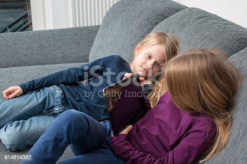 istock Mädchen versteckt Bildschirm vor jüngerer Schwester 914814032