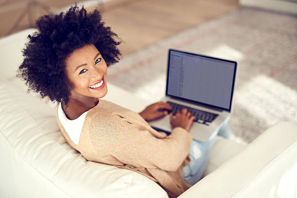 Me time is screen time Shot of a young woman using a laptop at home looking over shoulder stock pictures, royalty-free photos & images