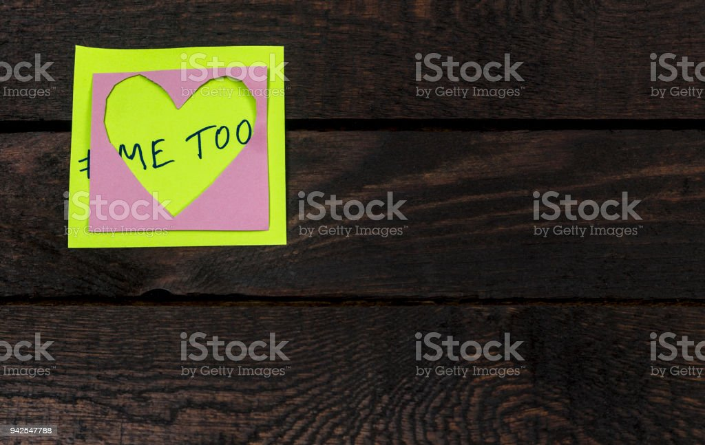 Me Too hashtag on a heart shaped adhesive note posted on a wooden background stock photo