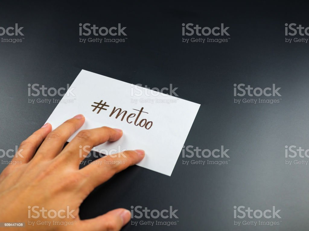 me too hashtag on paper card note with hand on background stock photo