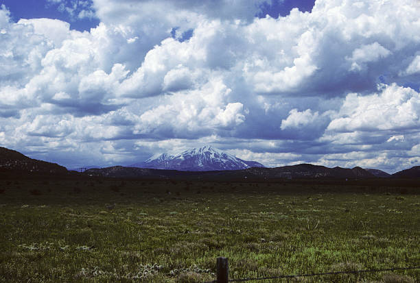 meadow and mountain, circa 1987 Meadow/pasture and extreme clouds, with snowcapped mountain in the distance. Near Fort Union National Monument. hearkencreative stock pictures, royalty-free photos & images